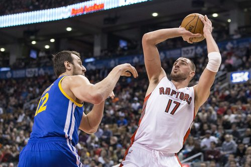 Toronto Raptors' Jonas Valanciunas, right, shoots against Golden State Warriors' Andrew Bogut during the first half of an NBA basketball game Sunday, March 2, 2014, in Toronto. (AP Photo/The Canadian Press, Chris Young)