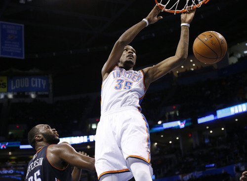 Oklahoma City Thunder forward Kevin Durant (35) dunks in front of Charlotte Bobcats center Al Jefferson (25) in the third quarter of an NBA basketball game in Oklahoma City, Sunday, March 2, 2014. Oklahoma City won 116-99. (AP Photo/Sue Ogrocki)