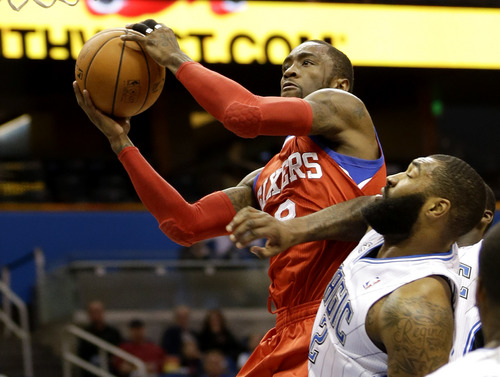 Philadelphia 76ers' Tony Wroten, top, goes to the basket past Orlando Magic's Kyle O'Quinn (2) during the first half of an NBA basketball game in Orlando, Fla., Sunday, March 2, 2014. (AP Photo/John Raoux)