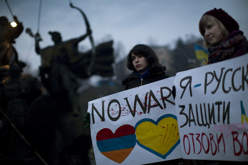 """Ukrainian Maria, 23, right, and Vanui, 22, hold posters against Russia's military intervention in Crimea, in Kiev, Ukraine, Sunday, March 2, 2014. Russia's parliament approved a motion to use the country's military in Ukraine after a request from President Vladimir Putin as protests in Russian-speaking cities turned violent Saturday, sparking fears of a wide-scale invasion. The poster in the right side reads in Ukrainian: """"I am from Russia, please protect me and remove the weapons and soldiers from Ukraine."""" (AP Photo/Emilio Morenatti)"""