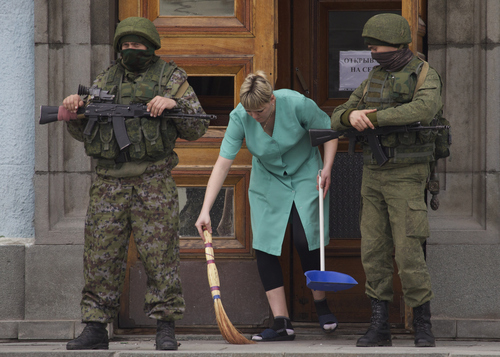 A woman sweeps away the broken glass as two unidentified armed men guard the entrance to the local government building in downtown Simferopol, Ukraine, on Sunday, March 2, 2014. A convoy of hundreds of Russian troops headed toward  Simferopol the regional capital of Ukraine's Crimea region on Sunday, a day after Russia's forces took over the strategic Black Sea peninsula without firing a shot. (AP Photo/Ivan Sekretarev)