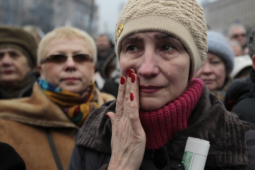 """A woman reacts, during a rally in Kiev's Independence Square, Sunday, March 2, 2014. Ukraine's new prime minister urged Russian President Vladimir Putin to pull back his military Sunday in the conflict between the two countries, warning that """"we are on the brink of disaster."""" The comments from Arseniy Yatsenyuk came as a convoy of Russian troops rolled toward Simferopol, the capital of Ukraine's Crimea region, a day after Russian forces took over the strategic Black Sea peninsula without firing a shot. (AP Photo/Sergei Chuzavkov)"""