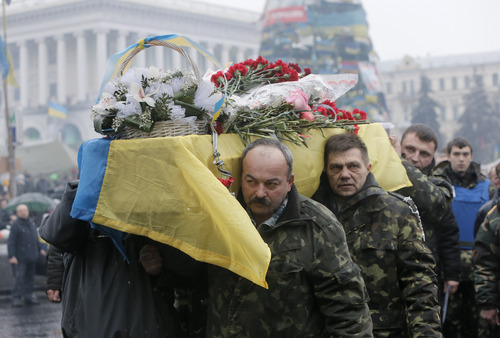 A coffin with the body of a protester killed in clashes with the police  is carried through the crowd in Independence Square, Kiev, Monday, March. 3, 2014. The United States and its allies in Europe are attempting to pressure Russia to reverse its military incursion into Ukraine, even as Moscow's troops dig in in parts of this former Soviet country after Kiev decided to oust the pro-Russia president. (AP Photo/Efrem Lukatsky)