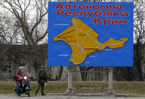 """A pro-Russian soldier stands by a billboard with a map of Crimea and bearing the words """"Autonomous Republic of Crimea"""" in the port of Kerch, Ukraine, Monday, March 3, 2014. Pro-Russian troops controlled a ferry terminal on the easternmost tip of Ukraine's Crimea region close to Russia on Monday, intensifying fears that Moscow will send even more troops into the strategic Black Sea region in its tense dispute with its Slavic neighbor. (AP Photo/Darko Vojinovic)"""