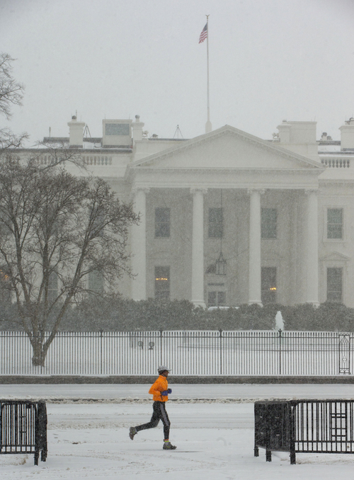 A jogger is seen in Lafayette Park in the snow front of the White House in Washington, Monday, March 3, 2014. The National Weather Service has issued a Winter Storm Warning for the greater Washington Metropolitan region, prompting area schools and the federal government to close for the wintry weather.  (AP Photo/Pablo Martinez Monsivais)