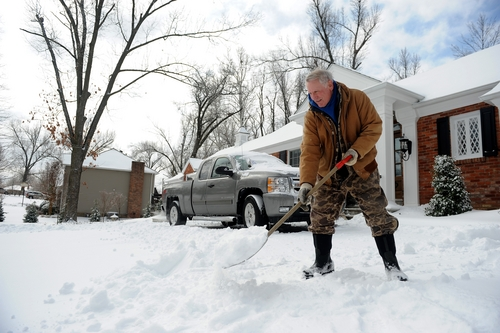 Gary McMillan, 73, of Paducah, Ky., shovels snow at his home in Paducah on Monday, March 3, 2014. A winter storm brought ice, sleet and snow to the region hampering travel and business. Area colleges, school and shopping centers have closed. (AP Photo/Stephen Lance Dennee)