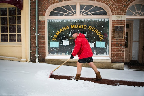 Owner of Bodywork Wayne Gootee shovels the walkway in front of businesses in Fredericksburg, Va during the snowstorm on Monday, March 3, 2014. Winter kept its icy hold on much of the country Monday, with snow falling and temperatures dropping as schools and offices closed and people from the South and Mid-Atlantic to Northeast reluctantly waited out another storm indoors. (AP Photo/The Free Lance-Star,  Autumn Parry)