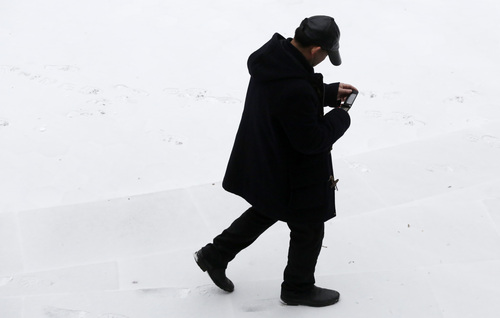 A man checks his mobile phone as he walks through snow-covered Columbus Park, Monday, March 3, 2014 in New York. Winter kept its icy hold on much of the country Monday, with snow falling and temperatures starting to plummet from the Mid-Atlantic states up to the East Coast. (AP Photo/Mark Lennihan)