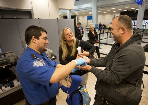 Lennie Mahler  |  The Salt Lake Tribune A TSA employee swabs hands and shoes of travelers who asked not to be identified in the expedited security line in Salt Lake City International Airport, Tuesday, March 4, 2014. Enrollment in the new TSA Pre-Check program grants passengers an ID number for $85 that allows access to the expedited security line for five years.