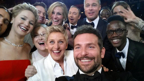 """This image released by Ellen DeGeneres shows actors front row from left, Jared Leto, Jennifer Lawrence, Meryl Streep, Ellen DeGeneres, Bradley Cooper, Peter Nyong'o Jr., and, second row, from left, Channing Tatum, Julia Roberts, Kevin Spacey, Brad Pitt, Lupita Nyong'o and Angelina Jolie as they pose for a """"selfie"""" portrait on a cell phone during the Oscars at the Dolby Theatre on Sunday, March 2, 2014, in Los Angeles. (AP Photo/Ellen DeGeneres)"""