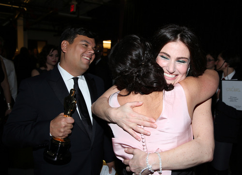 "Robert Lopez, left, looks on as his wife Kristen Anderson-Lopez is embraced by Idina Menzel backstage after the couple won the award for best original song in a feature film for ""Let It Go"" from ""Frozen"" during the Oscars at the Dolby Theatre on Sunday, March 2, 2014, in Los Angeles.  (Photo by Matt Sayles/Invision/AP)"