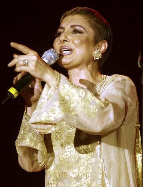 "FILE - In this March 21, 2001 file photo Iranian pop star Googoosh performs during a concert in Dubai, United Arab Emirates. Googoosh has released a video that addresses homosexual love, a major gesture by one of the country's top cultural figures in exile, causing shockwaves in the Islamic republic. Googoosh sings ""don't tell me to stop loving: you can't do that and I can't either."" Googoosh was Iran's first pop diva, though the 1979 revolution ended her live singing career for two decades until she immigrated to the West. Navid Akhavan, an Iranian-born German who wrote and directed the video for Googoosh's song ""Behesht"" (Heaven), said it has been viewed by more than a million Iranians online or via illegal satellite channels since its Valentine's Day release. (AP Photo/Kamran Jebreili, File)"