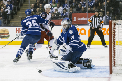 Toronto Maple Leafs goalie James Reimer, right, makes a save as Leafs' Carl Gunnarsson, left, covers Columbus Blue Jackets' Ryan Johansen  during the first period of an NHL hockey game in Toronto on Monday, March 3, 2014. (AP Photo/The Canadian Press, Chris Young)