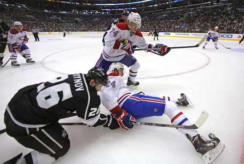 Los Angeles Kings defenseman Slava Yoynov (26), of Russia, and Montreal Canadiens defenseman Jarred Tinordi (24) and defenseman Alexei Emelin (74), of Russia, tangle in the second period of an NHL hockey game in Los Angeles, Monday, March 3, 2014. (AP Photo/Reed Saxon)