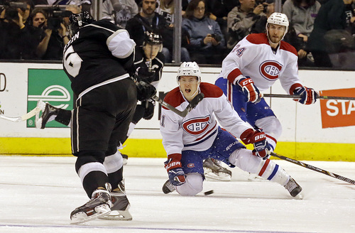 Montreal Canadiens right winger Brendan Gallagher (11) and defenseman Jarred Tinordi (24) defend as Los Angeles Kings defenseman Jake Muzzin (6) shoots in the third period of an NHL hockey game in Los Angeles, Monday, March 3, 2014. The Kings won, 2-1. (AP Photo/Reed Saxon)