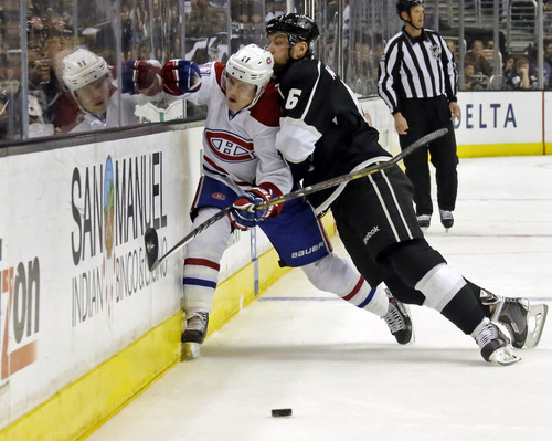 Montreal Canadiens right winger Brendan Gallagher (11) and Los Angeles Kings defenseman Jake Muzzin (6) tangle in the first period of an NHL hockey game in Los Angeles, Monday, March 3, 2014. The Kings won, 2-1. (AP Photo/Reed Saxon)