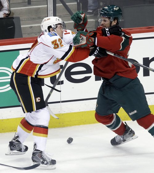 Calgary Flames' Paul Byron, left, and Minnesota Wild's Nate Prosser do some shoving as the puck rolls between them in the first period of an NHL hockey game, Monday, March 3, 2014, in St. Paul, Minn. (AP Photo/Jim Mone)