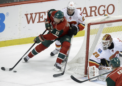 Minnesota Wild's Dany Heatley, left, cuts the corner as he is pursued by Calgary Flames' Sean Monahan as goalie Reto Berra, right, defends the net in the first period of an NHL hockey game, Monday, March 3, 2014, in St. Paul, Minn. (AP Photo/Jim Mone)