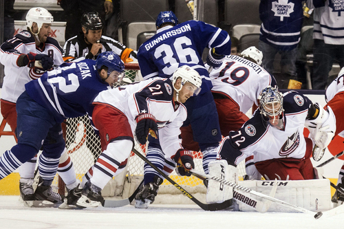 Columbus Blue Jackets goaltender Sergei Bobrovsky, right, watches as James Wisniewski, center, scrambles the puck away from Toronto Maple Leafs Tyler Bozak, left, during the first period of an NHL hockey game in Toronto on Monday, March 3, 2014. (AP Photo/The Canadian Press, Chris Young)