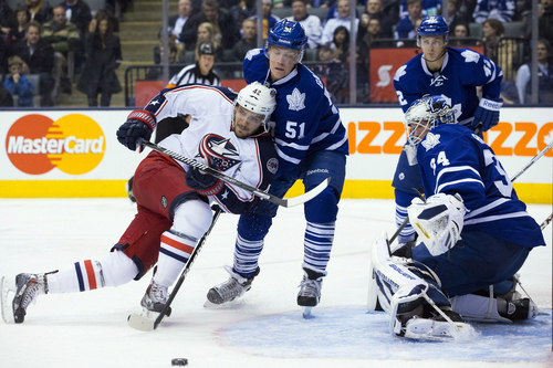 Columbus Blue Jackets' Artem Anisimov, left, and Toronto Maple Leafs' Jake Gardiner, center, scramble for a loose puck as Leafs' goalie James Reimer, right, is near during the third period of an NHL hockey game in Toronto on Monday, March 3, 2014.  (AP Photo/The Canadian Press, Chris Young)