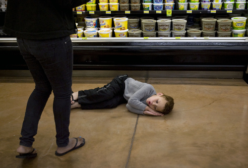 Kim Raff  |  The Salt Lake Tribune Overwhelmed by the bright lights and loud noises at the grocery sore, James Turner curls up on the floor. The Stansbury Park boy has autism and his therapist (left) seizes upon the moment as a teaching opportunity, April 6, 2013.