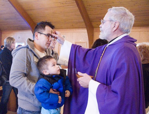 Sergio Woo holds up his son Anthony Woo, 2, as Rev. Robert Moran places ashes on his forehead during an Ash Wednesday Mass Wednesday, March 5, 2014, at Immaculate Conception Catholic Church in Portland, Ind. Christians around the world observed Ash Wednesday, which marks the first day of Lent. (AP Photo/The Commercial Review, Kelly Lynch)