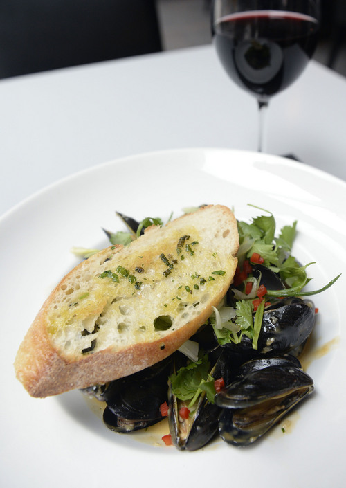 Al Hartmann  |  The Salt Lake Tribune  Stone Oven Fired Mussels appetizer with coconut red curry, sesame oil and scallions at Bistro 222.