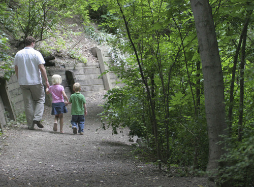 | Tribune File Bountiful residents Kelly Passy and his daughter Bailey(6) and son Noah (4), walk the trails in Miller Park. 7/21/05