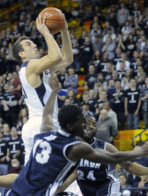 Utah State guard/forward Spencer Butterfield takes a shot over Nevada forward Cole Huff (13), and guard Deonte Burton during their game, Wednesday, Feb. 5, 2014, in Logan, Utah. (Eli Lucero/Herald Journal)