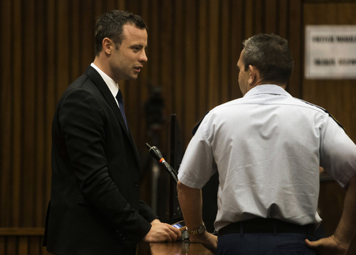 Oscar Pistorius, left, stands in the dock on the fourth day of his trial at the high court in Pretoria, South Africa, Thursday, March 6, 2014.  Pistorius is charged with murder for the shooting death of his girlfriend Reeva Steenkamp on Valentine's Day in 2013. (AP Photo/Marco Longari, Pool)