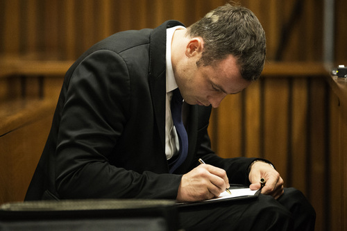 Oscar Pistorius writes notes while sitting in the dock on the fourth day of his trial at the high court in Pretoria, South Africa, Thursday, March 6, 2014.  Pistorius is charged with murder for the shooting death of his girlfriend Reeva Steenkamp on Valentine's Day in 2013. (AP Photo/Marco Longari, Pool)