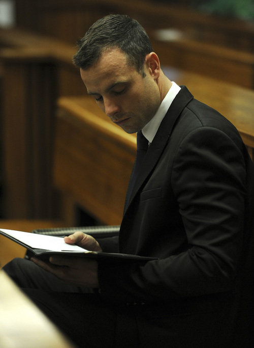 Oscar Pistorius sits in the dock on the fourth day of his trial at the high court in Pretoria, South Africa, Thursday, March 6, 2014.  Pistorius is charged with murder for the shooting death of his girlfriend Reeva Steenkamp on Valentine's Day in 2013. (AP Photo/Werner Beukes, Pool)