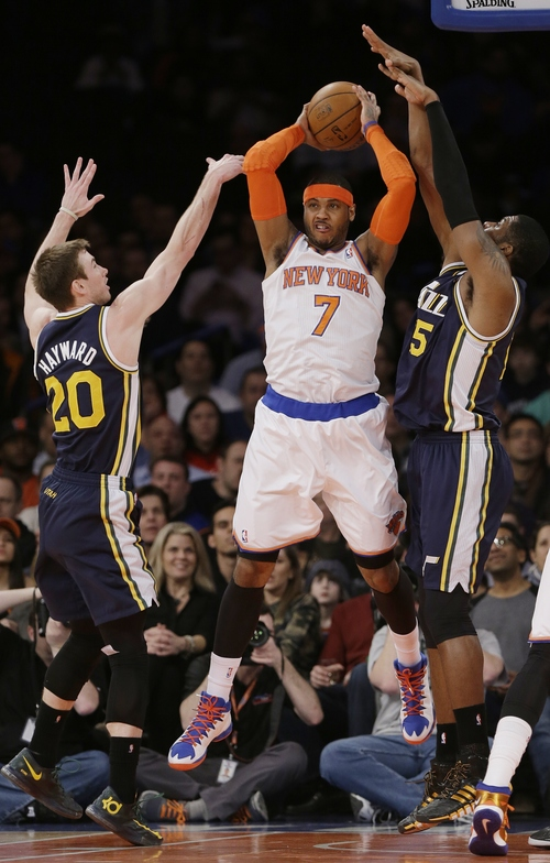 New York Knicks' Carmelo Anthony (7) passes away from Utah Jazz's Gordon Hayward (20) and John Lucas III (5) during the first half of an NBA basketball game on Friday, March 7, 2014, in New York. (AP Photo/Frank Franklin II)