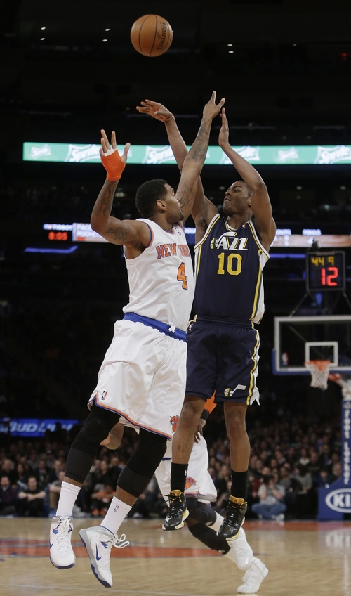 Utah Jazz's Alec Burks (10) shoots over New York Knicks' Jeremy Tyler (4) during the first half of an NBA basketball game on Friday, March 7, 2014, in New York. (AP Photo/Frank Franklin II)