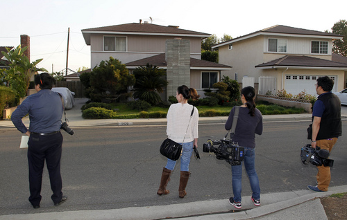 Japanese media wait outside the residence, left, of Dorian S. Nakamoto Thursday March 6, 2014, in Temple City, Calif. Nakamoto, the man that Newsweek claims is the founder of Bitcoin denies he had anything to do with it and says he had never even heard of the digital currency until his son told him he had been contacted by a reporter three weeks ago.   (AP Photo/Nick Ut)