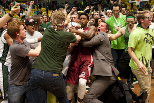 In this Thursday, Feb. 27, 2014 photo, New Mexico State's Daniel Mullings, at center in red and white jersey, is involved in a brawl involving players and fans who came onto the court when New Mexico State guard K.C. Ross-Miller hurled the ball at Utah Valley's Holton Hunsaker seconds after the Wolverines' 66-61 overtime victory against the Aggies.  (AP Photo/The Daily Herald, Grant Hindsley)