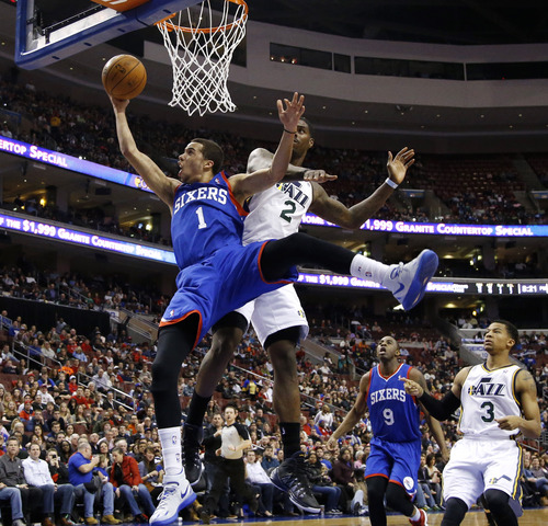 Philadelphia 76ers' Michael Carter-Williams (1) goes up to shoot against Utah Jazz's Marvin Williams (2) during the first half of an NBA basketball game on Saturday, March 8, 2014, in Philadelphia. (AP Photo/Matt Slocum)