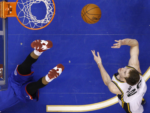 Utah Jazz's Gordon Hayward, right, goes up for a shot past a fallen Philadelphia 76ers' Thaddeus Young during the second half of an NBA basketball game, Saturday, March 8, 2014, in Philadelphia. (AP Photo/Matt Slocum)