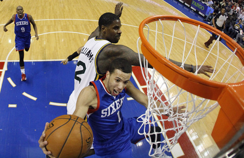 Philadelphia 76ers' Michael Carter-Williams (1) goes up to shoot against Utah Jazz's Marvin Williams (2) during the first half of an NBA basketball game on Saturday, March 8, 2014, in Philadelphia. Utah won 104-92. (AP Photo/Matt Slocum)