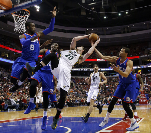 Utah Jazz's Gordon Hayward (20) tries to shoot past Philadelphia 76ers' Tony Wroten (8), Jarvis Varnado (40) and Michael Carter-Williams (1) during the second half of an NBA basketball game on Saturday, March 8, 2014, in Philadelphia. Utah won 104-92. (AP Photo/Matt Slocum)