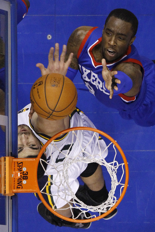 Philadelphia 76ers' Tony Wroten, top, battles for a rebound with Utah Jazz's Enes Kanter during the first half of an NBA basketball game on Saturday, March 8, 2014, in Philadelphia. (AP Photo/Matt Slocum)