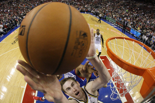Utah Jazz's Gordon Hayward, bottom, goes up to shoot as Philadelphia 76ers' Thaddeus Young defends during the second half of an NBA basketball game on Saturday, March 8, 2014, in Philadelphia. Utah won 104-92. (AP Photo/Matt Slocum)