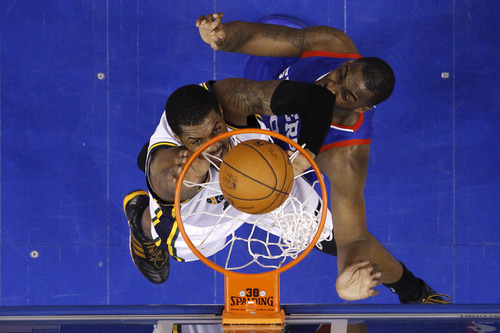 Utah Jazz's Derrick Favors, left, goes up for a dunk against Philadelphia 76ers' Jarvis Varnado during the second half of an NBA basketball game on Saturday, March 8, 2014, in Philadelphia. (AP Photo/Matt Slocum)