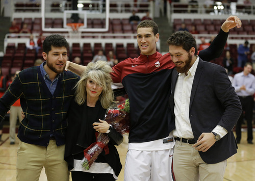 Stanford forward Dwight Powell, second from right, greets friends from left, Omar Nazmi, Theresa Morgan, and Ahmed Nazmi while being honored on senior day before the start of an NCAA college basketball game against Utah Saturday, March 8, 2014, in Stanford, Calif. Powell's mother, Jacqueline Weir, died in September 2012 after a short fight with cancer. (AP Photo/Eric Risberg)