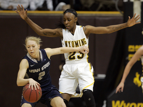 Wyoming's Chelan Landry guards Utah State's Elise Nelson on Tuesday, March 4, 2014 at the Arena-Auditorium in Laramie. The Wyoming Cowgirls lost 84-80 to Utah State in their final home game of the season. (AP Photo/Star-Tribune, Alan Rogers)