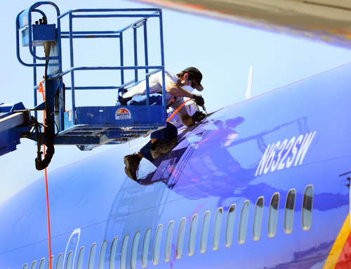 File- This April 3, 2011, file photo shows a member of the National Transportation and Safety Board investigating the emergency landing of Southwest Airlines flight 812 cutting away a portion of the planes fuselage in Yuma, Ariz.  (AP Photo/The Yuma Daily Sun, Craig Fry, File)