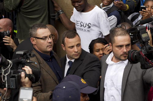 Oscar Pistorius, center, is escorted out by police officers as he leaves  the high court on the second day of his trial in Pretoria, South Africa, Monday, March 3, 2014. Oscar Pistorius is charged with murder for the shooting death of his girlfriend, Reeva Steenkamp, on Valentines Day in 2013. (AP Photo/Themba Hadebe)