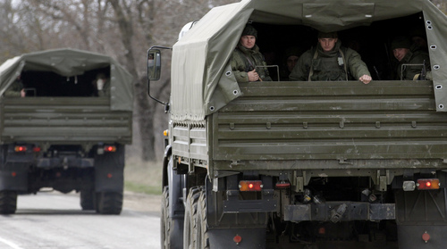Uniformed men look out of military vehicles bearing no license plates as they travel on the road from Feodosia to Simferopol in the Crimea, Ukraine, Saturday, March 8, 2014. More than 60 military trucks bearing no license plate numbers was headed from the eastern city of Feodosia toward the city of Simferopol, the regional capital. (AP Photo/Darko Vojinovic)