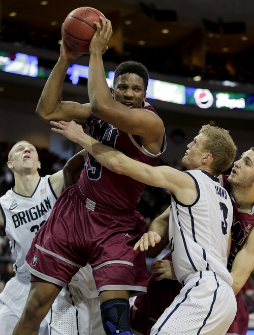 Loyola Marymount's Alex Osborne, center, grabs a rebound against BYU's Tyler Haws in the second half of a quarterfinal West Coast Conference NCAA college basketball tournament game on Saturday, March 8, 2014, in Las Vegas. BYU won 85-74. (AP Photo/Julie Jacobson)