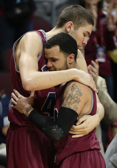 Loyola Marymount's Marin Mornar, left, hugs Anthony Ireland near the end of the second half of a quarterfinal West Coast Conference NCAA college basketball tournament game against BYU, Saturday, March 8, 2014, in Las Vegas. BYU won 85-74. (AP Photo/Julie Jacobson)